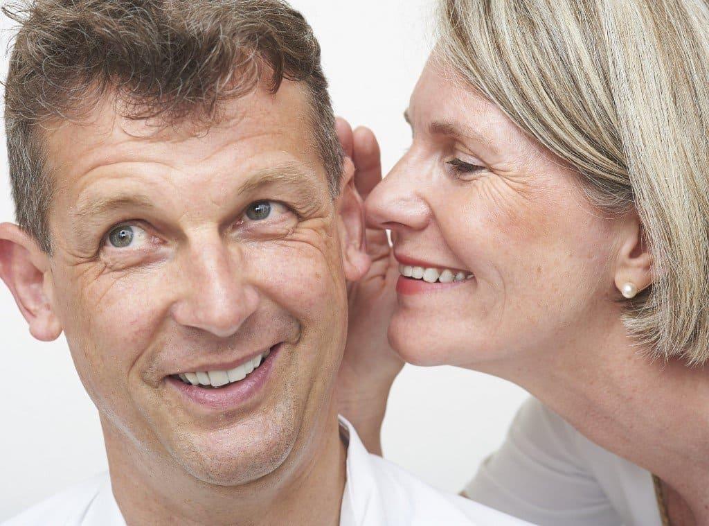 Frau flüstert Mann mit Hörgerät ins Ohr