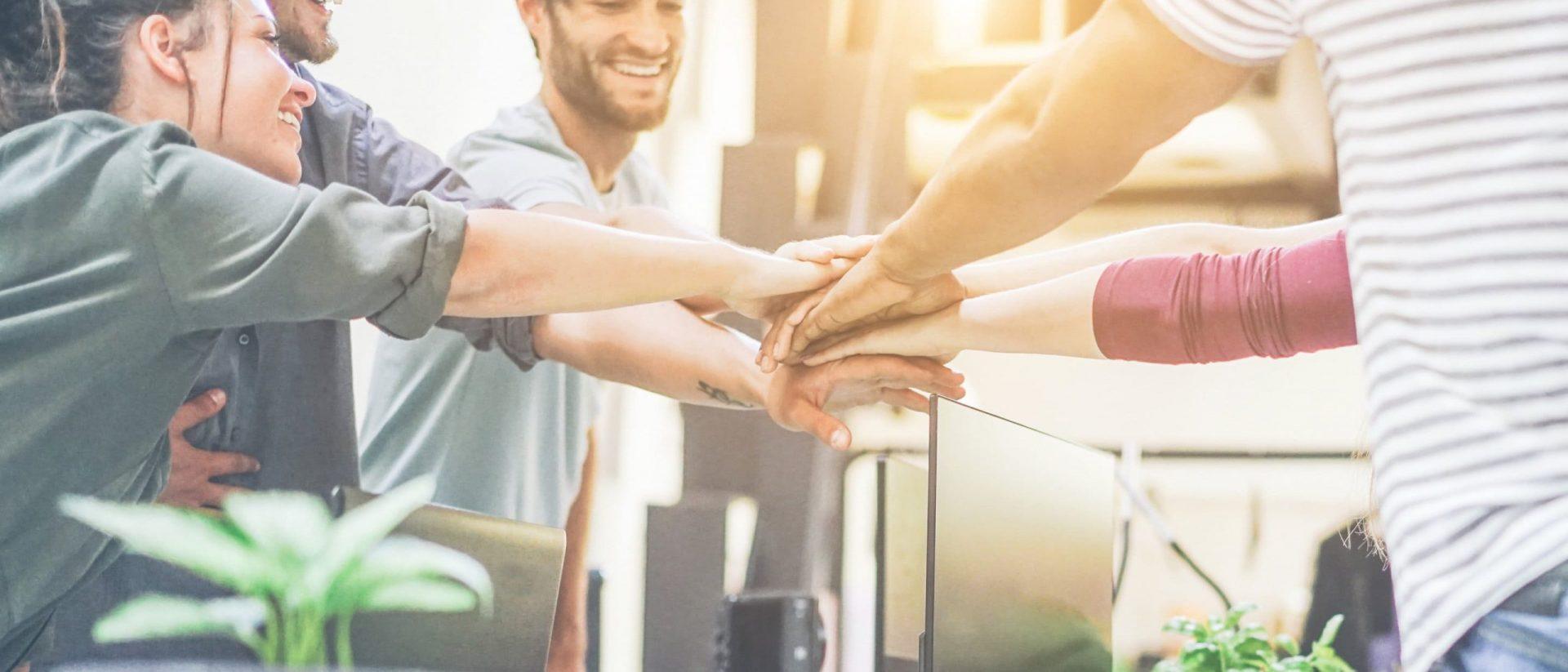 Team mit Hände übereinander im Büro